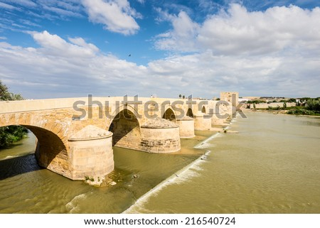 Old Roman bridge over the Guadalquivir River in Cordoba, Spain. This bridge has been restored many times. UNESCO World Heritage Site. - stock photo