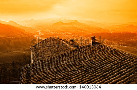 old roof of the house on the hill at sunset