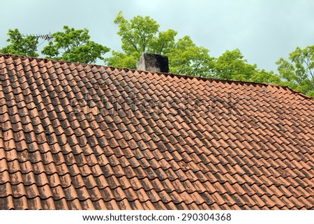 Old roof tile pattern over blue sky - stock photo