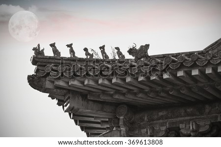 Old roofs at the Forbidden city and a big moon in Beijing - stock photo