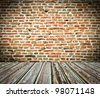 Old room with brick wall and wooden floor - stock photo