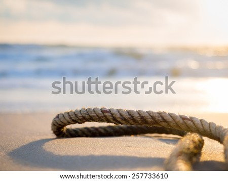 Old rope on the beach at sunrise - stock photo