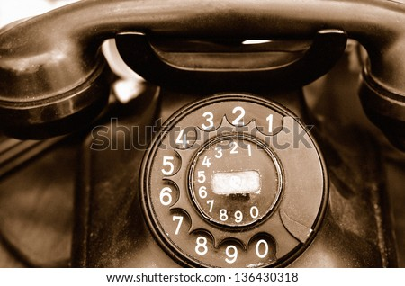 Old rotary telephone close-up. Sepia with grain added. - stock photo