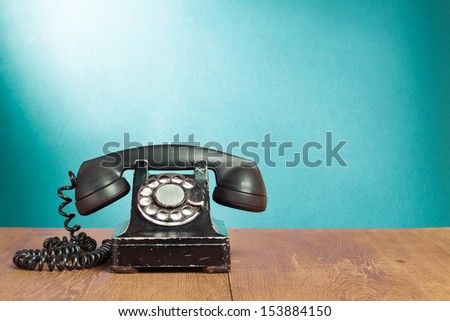 Old rotary telephone on wood table for retro background - stock photo