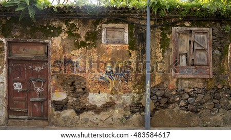 Old rotten wall structure with wooden door and graffitti