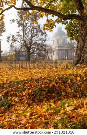 Old rotunda church in the village among autumn trees. - stock photo