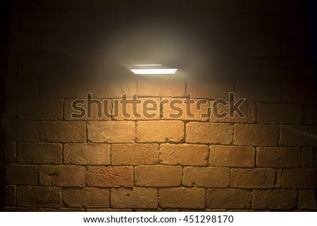Old rough brick wall background texture with a spotlight shining on it