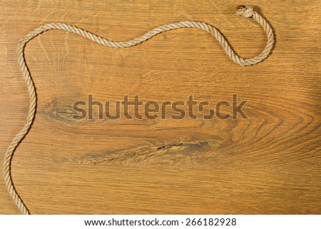 Old, rough rope with a knot on a wooden background - stock photo