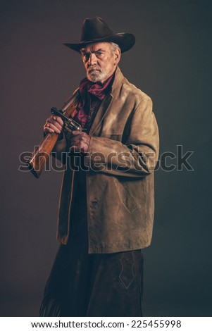 Old rough western cowboy with gray beard and brown hat holding rifle and revolver. Low key studio shot. - stock photo