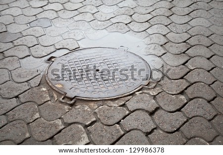 Old round steel sewer manhole on the cobblestone road - stock photo
