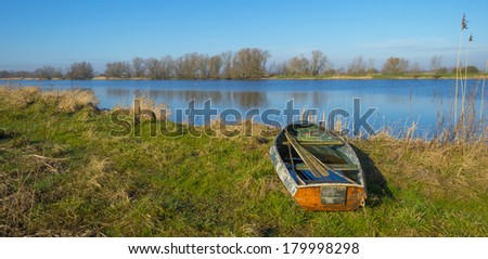 Old rowboat on the shore of a river - stock photo