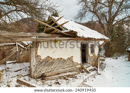 Old ruined abandoned house among trees in the winter - stock photo