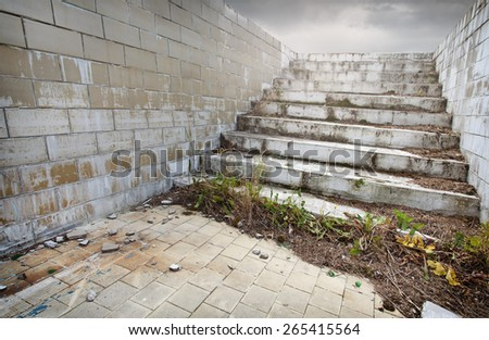 Old ruined abandoned swimming pool with stairs - stock photo