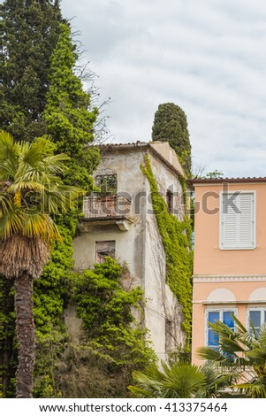 Old ruined and abandoned house hidden behind the foliage and new house. - stock photo