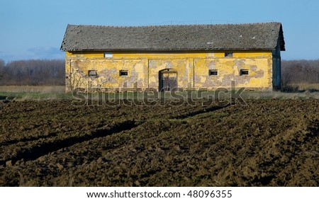 Old, ruined barn on a farmland with plowed fields
