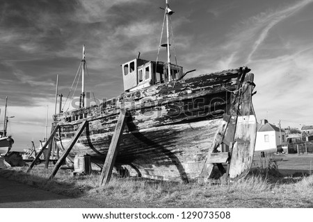 Old ruined boat at Burghead harbour, Scotland, awaiting restoration.