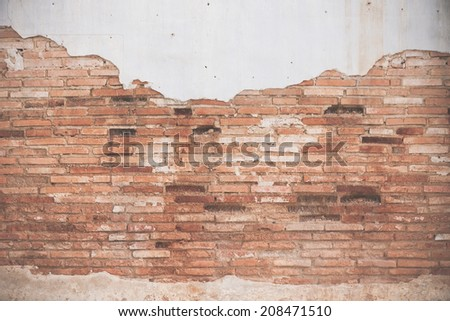 Old ruined brick wall with peeling of plaster - stock photo