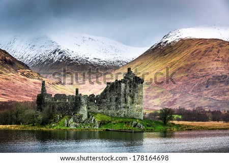 Old ruined castle on the background of snowy mountains - stock photo