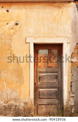 Old ruined facade with just an wooden door - stock photo