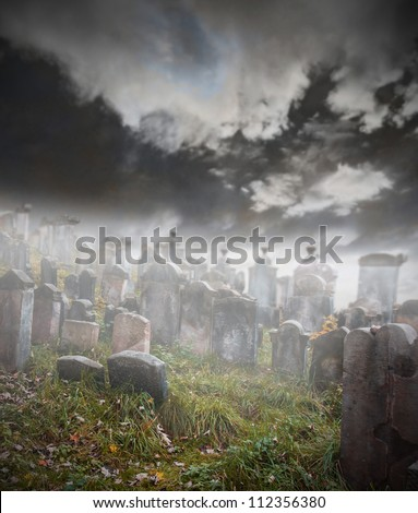 Old ruined graveyard in mystery fog - stock photo