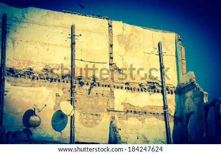 Old ruined house with two rusty satellite dishes and birds (pigeons) sitting over the wall. Nobody.  Life is going on idea. Aged photo. - stock photo