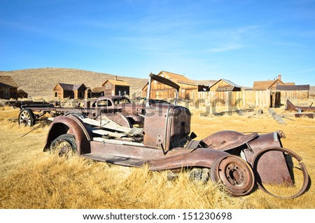 Old ruined metal car in ghost town - stock photo