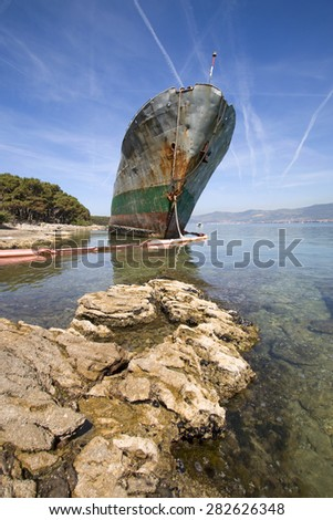 Old ruined ship aground on beach after shipwreck in the storm - stock photo