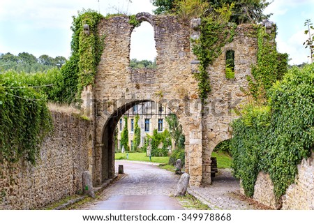 Old ruins of the entrance gate to the Abbaye des Vaux de Cernay in France.  - stock photo