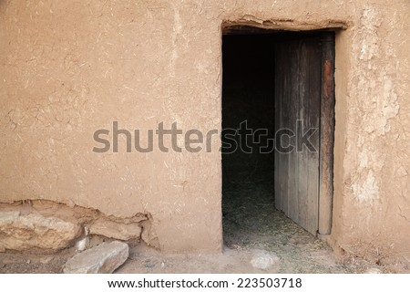 Old rural clay wall with open wooden door. Background texture - stock photo