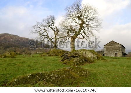 Old rural country stone farmhouse as the winter fog lifts in Ambleside, Lake District, in Northern England. - stock photo
