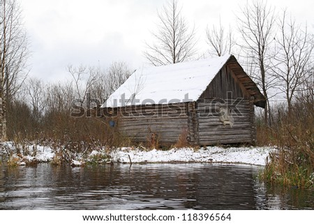 old rural house on river coast - stock photo