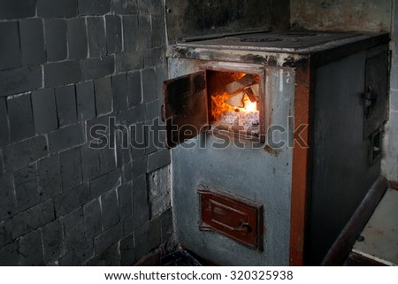 Old rural wood stove with the burning firewood. Alternative energy source background - stock photo