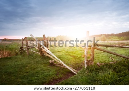 old rural wooden fence on sunrise, natural summer background - stock photo