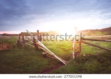 old rural wooden fence on sunrise, natural summer background with vintage instagram effect - stock photo