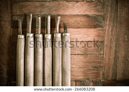 old & rust carpenter wood carving chisel tool on wooden background - stock photo