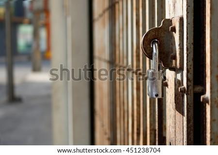Old rust metal door locked with silver padlock closeup - stock photo