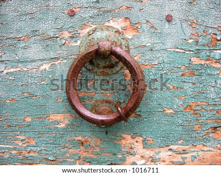 Old rust ring door knocker on a peeling paint wood door