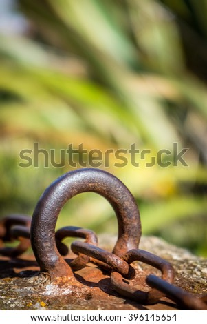 Old rusted chain attached to the stone wall in the port - stock photo
