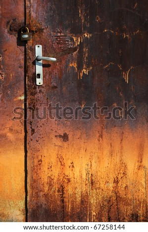 Old rusted door with padlock - stock photo