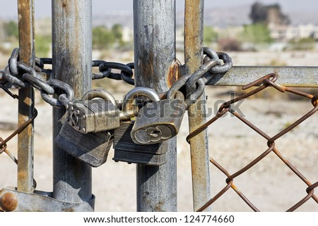 Old rusted gate chain together with several locks.