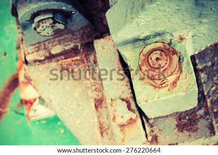 Old rusted industrial details, nuts and bolt, selective focus, shallow DOF, vintage toned photo with old instagram style filter effect - stock photo