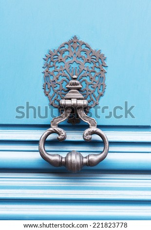 Old rusted knocker on blue wooden door in Paris, France - stock photo