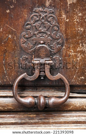 Old rusted knocker on brown wooden door in Paris, France - stock photo