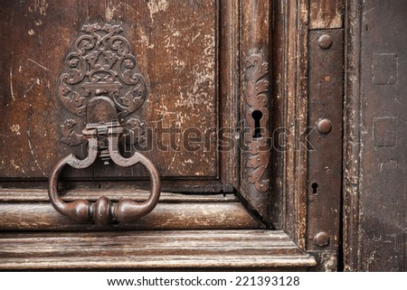 Old rusted knocker on brown wooden door. Paris, France - stock photo