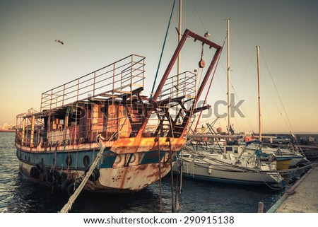 Old rusted pleasure boat is moored in Nesebar, ancient historical town, Bulgaria. Vintage retro stylized photo with tonal correction filter, instagram style  - stock photo