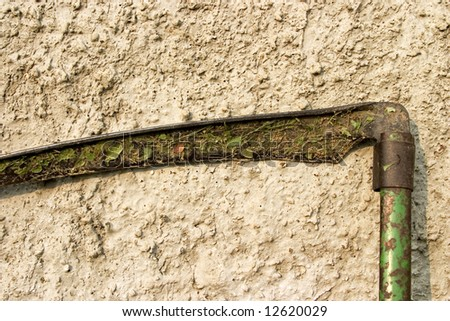 Old rusted scythe standing against yellow stone wall - stock photo
