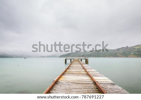 Old rustic jetty with railways on a stormy and rainy day at a bay on the Banks Peninsula, Christchurch, New Zealand, South Island