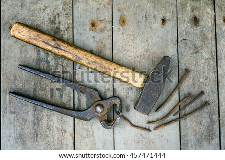 Old rustic pliers with a hammer and rusty nail on the wooden background with space for text. Vintage look. - stock photo
