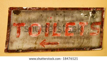 old rustic sign showing way to toilets on yellow wall with red lettering
