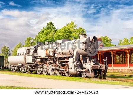 Old rustic steam locomotive on station platform. Cloudy sky background. Summertime outdoors. - stock photo
